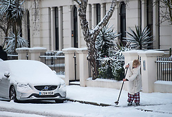© Licensed to London News Pictures. 28/02/2018. London, UK. A woman sweeps snow form the pavement in picturesque scenes in Little Venice, West London following heavy snowfall last night. Large parts of the UK are experiencing disruption as 'Storm Emma' hits, following Russian a cold front earlier in the week named 'The Beast From The East'. Photo credit: Ben Cawthra/LNP
