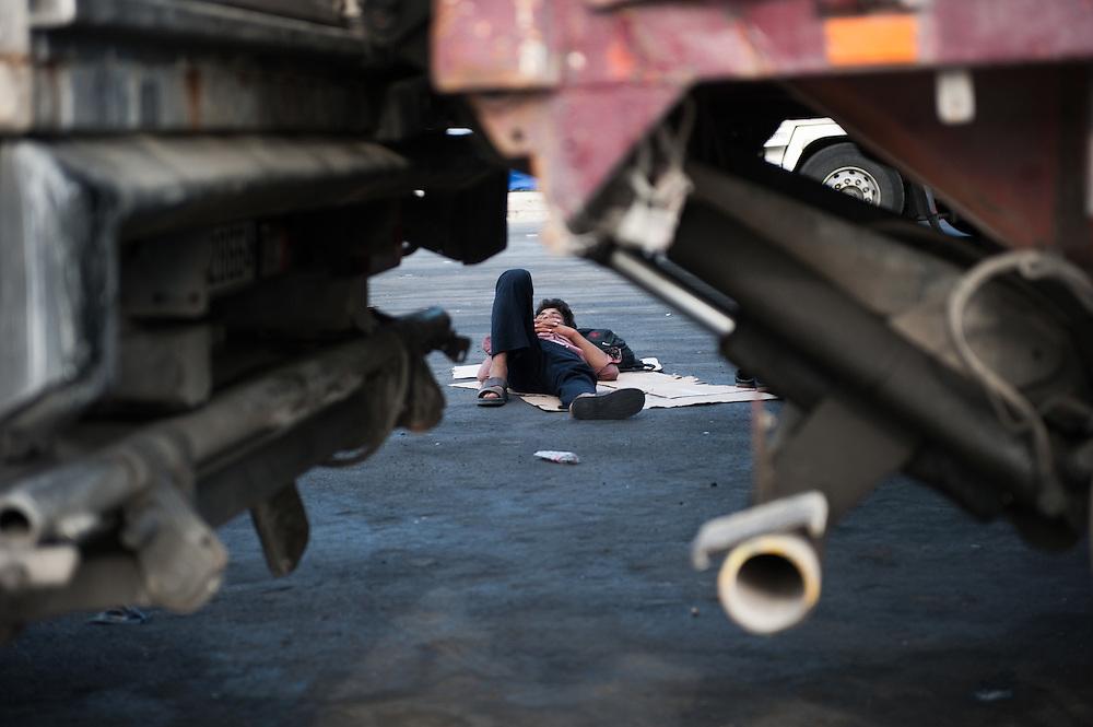An Afghan man sleeping rough in the port of Mytiline between parked lorries.