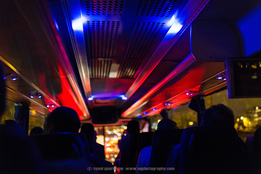 The lights of emergency vehicles are reflected in the roof of a passenger coach as it passes the site of a motor accident at night in Casablanca, Morocco on 9 September 2013.