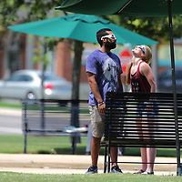 Rogelio Realzola and Casey Miller both from Starkville take turns looking at the solar eclipse from Fairpark in Tupelo.