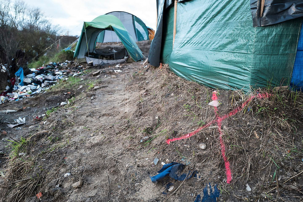 """© Licensed to London News Pictures. 12/01/2016. London, UK. Pink markings on the ground and on buildings to lay out the location of a new """"buffer zone at the migrant camp in Calais referred to as the Jungle. French authorities have announced they are creating a 100m buffer zone between the edge of the 'Jungle' camp and the motorway. Aid agencies estimate this will displace around 1700 people, including 300 women and 60 children. Photo credit: Rob Pinney/LNP"""