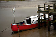 Red and white boat in mud at low tide, River Deben, Melton, Suffolk, England