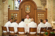 Bishop David Ricken meets with six candidates for ordination to the diaconate prior to their ordination at St. Francis Xavier Cathedral in Green Bay May 21. Bishop Ricken joined the men in the cathedral sanctuary before Mass and led them in prayer. (Sam Lucero | THe Compass)