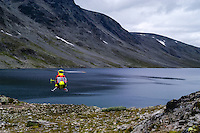 Norway, Jotunheimen. Hiking the famous Besseggen mountain ridge on the northern side of the Gjende Lake. Helicopter at Bessvatnet lake.