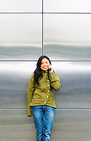 An early 30's / late 20's Asian woman talking on her cell phone in front of metal panels..Model Release: 20070513_MR_A