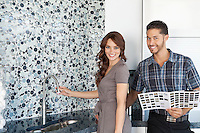 Portrait of beautiful young couple with color samples standing in model home kitchen