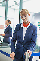 Portrait of young attractive passenger service agent opening the gate for boarding in airport