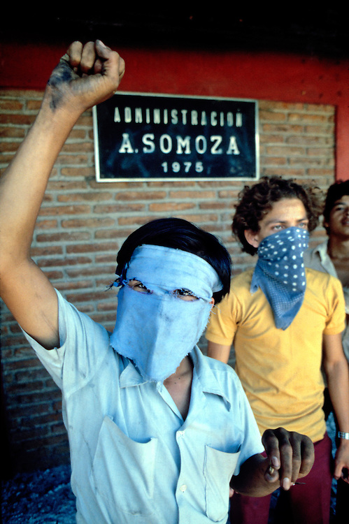 A teenage rebel Sandinista supporter defiantly raises a homemade contact grenade in Masaya, Nicaragua Civil War in Nicaragua - 1978. The grenades were made by wrapping black powder (gunpowder) with metal screws and nails in layers of paper tape. The grenade would explode when thrown against a hard surface causing damage and injury from the metal shrapnel.