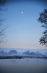 © Licensed to London News Pictures. 17/01/2017. Ripley, UK.  near Ripley. The moon sets over the River Wey near Ripley at first light. Cold temperatures are set to continue for most of the United Kingdom. Photo credit: Peter Macdiarmid/LNP