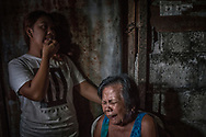 Weeping wife of Francisco Remedillo, rambles seemingly incoherently after he and and his adopted son were gunned down in front of her in an extrajudicial killing, Marlon Dela Cruz, 36, by masked assassins the only bedroom in their little house.  Francisco had attempted to ward off the assassins, to no avail, with a stick.  Quezon City, Philippines.