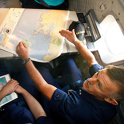 U.S. Coast Guard Rear Admiral Paul Zunkunft the Federal On Scene Coordinator for the gulf oil spill reviews a map of the source site prior to a flight on a C-144 U.S. Coast Guard Aircraft that flew over the source of the BP Plc Deep Water Horizon oil spill site in the Gulf of Mexico off the coast of Louisiana, U.S., on Sunday, July 11, 2010. Oil is once again gushing freely into the Gulf of Mexico as BP Plc is in the process of changing out the cap from the leaking well and plans to have a new cap installed over the next few days that will allow for oil to be captured efficiently. Photographer: Derick E. Hingle/Bloomberg