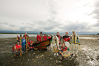 members of the Komok's First Nation dressed up in traditional regalia come ashore in a dugout canoe to dance and officially open the annual shellfish celebration held in Comox.  Comox Valley, Vancouver Island, British Columbia, Canada.