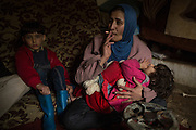 Aramoun, LEBANON: Sara's mother with her two older children in their damp, leaky shack. Originally from Yabroud, Syria, she says her baby never would have died if they had remained in their village. Their home was looted and destroyed by a rocket soon after they left it last year. Liam Maloney/Polaris Images