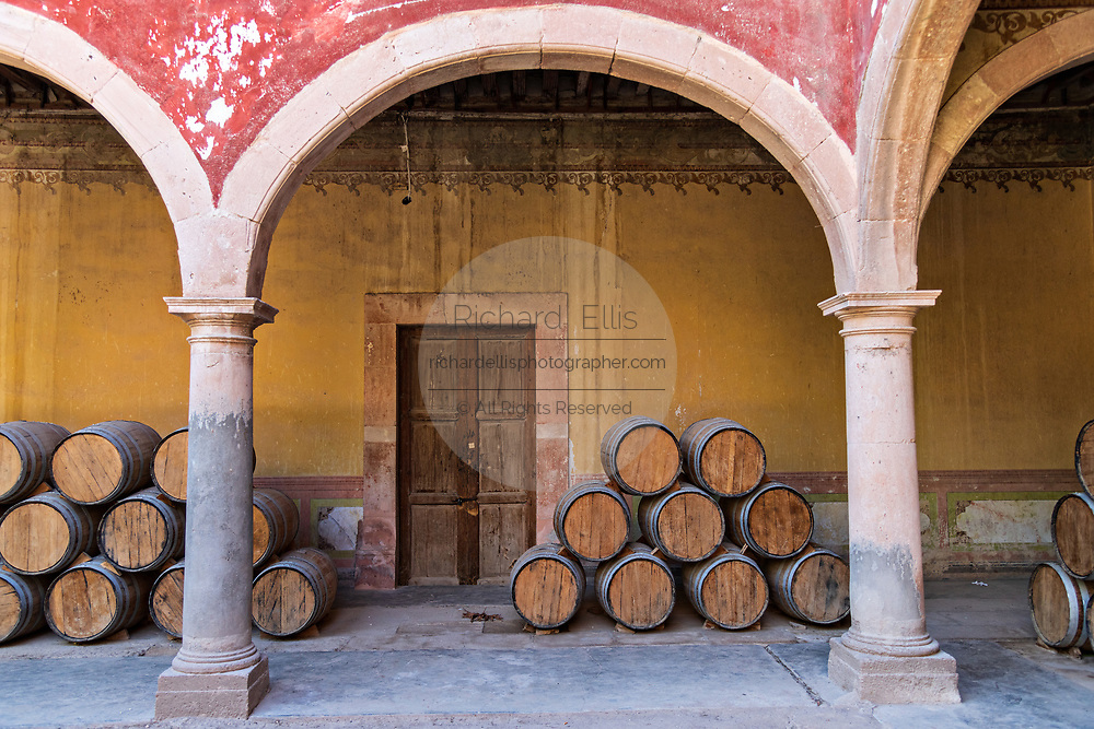 White oak barrels filled with Mezcal age under the derelict arches of the Hacienda de Jaral de Berrio in Jaral de Berrios, Guanajuato, Mexico. The abandoned Jaral de Berrio hacienda was once the largest in Mexico and housed over 6,000 people on the property and is credited with creating Mescal.