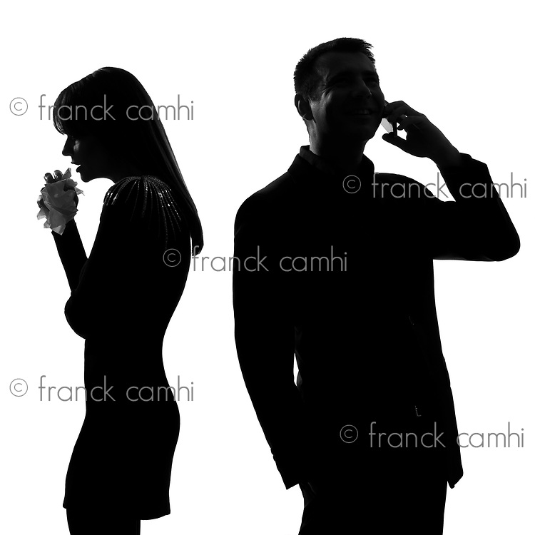 one caucasian couple standing back to back man on the phone  and woman crying in studio silhouette isolated on white background