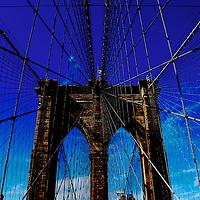 Image of Brooklyn Bridge against dark blue sky, New York City.