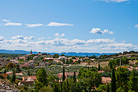 Beautiful countryside and village under a blue sky and fluffy clouds near Saint-Remy-de-Provence, southern France.