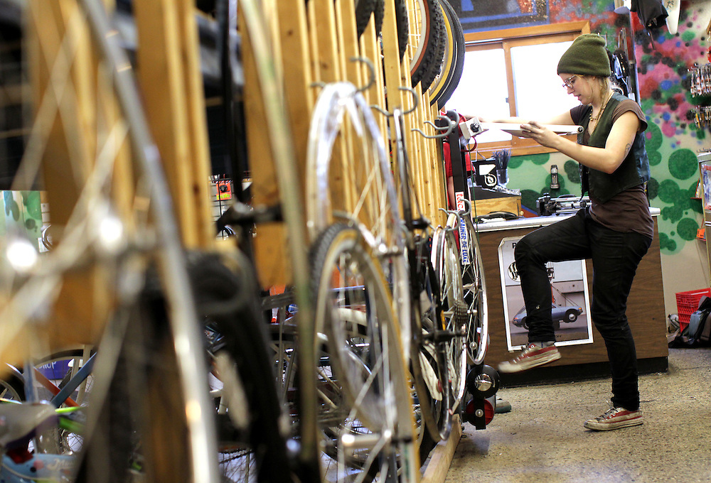 Assistant manager Alice Brandt, 23, adjusts a display at Express Bike Shop in St. Paul, Minnesota.  Brandt oversees youth apprentices who work part time at the shop where they learn mechanical skills related to fixing bicycles, as well as customer relation and entrepreneurial skills.