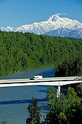 Motorhome crosses the bridge over the Chulitna River with Mt McKinley  behind.