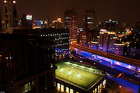 Tennis court at night with a motorway in the heart of Shanghai.