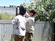 Affordable Fence & Gates crew makes sure the screen is level before welding it to the existing structure.