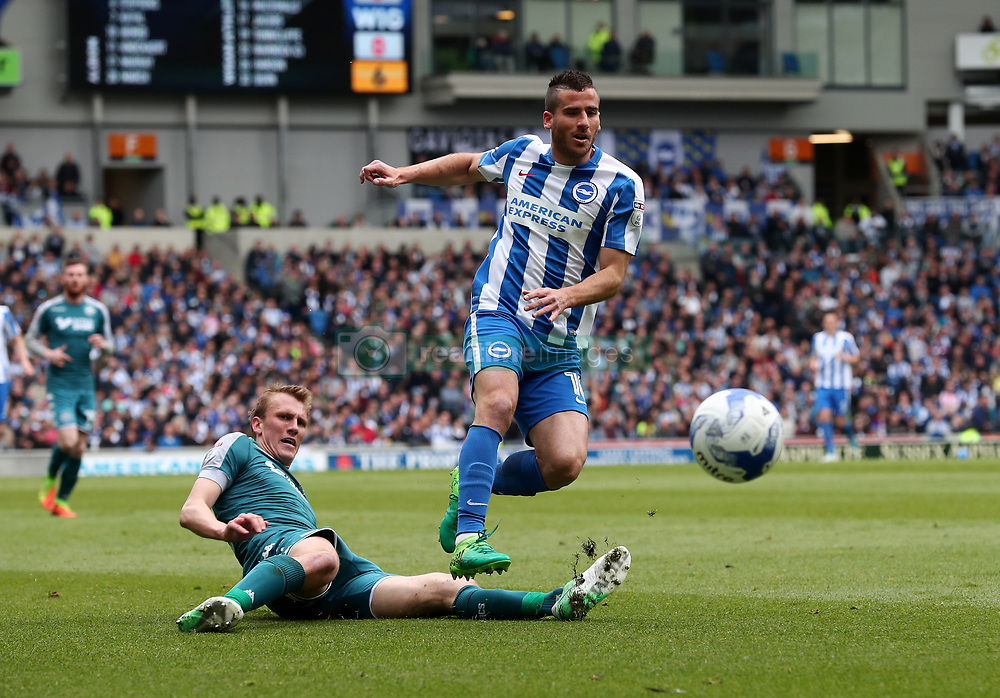 Brighton and Hove Albion's Tomer Hemed (right) is challenged by Wigan Athletic's Dan Burn during the Sky Bet Championship match at the AMEX Stadium, Brighton.