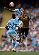 Aaron Ramsey of Arsenal (right) jumps for the ball with Fernandinho of Manchester City during the Barclays Premier League match at the Etihad Stadium, Manchester<br /> Picture by Russell Hart/Focus Images Ltd 07791 688 420<br /> 08/05/2016