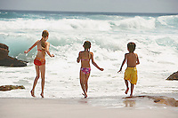 Three children (5-6 7-9 10-12) running on beach back view