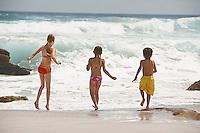 Three children (5-6 7-9 10-12) running on beach back view
