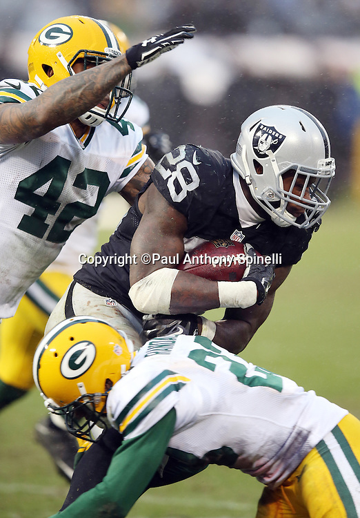 Oakland Raiders running back Latavius Murray (28) gets gang tackled by Green Bay Packers strong safety Morgan Burnett (42) and Green Bay Packers rookie cornerback Damarious Randall (23) as he runs for a fourth quarter gain of 7 yards during the 2015 week 15 regular season NFL football game against the Green Bay Packers on Sunday, Dec. 20, 2015 in Oakland, Calif. The Packers won the game 30-20. (©Paul Anthony Spinelli)