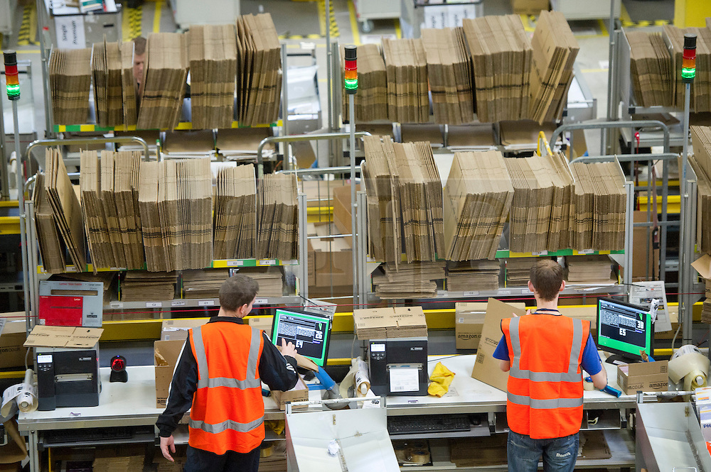 """© London News Pictures. File pic dated. 13/12/2012. Swansea, UK. A BBC investigation into a UK-based Amazon warehouse has found conditions that a stress expert said could cause """"mental and physical illness"""". PICTURED - Staff at the Amazon Swansea fulfilment centre process orders as they prepare their busiest time of the year. The 800,000 sq ft fulfilment centre, the largest of Amazon's plants in England and Whales, is big enough to hold 10 football pitches. Over 1,000 extra jobs are created at the centre to cope with the extra seasonal workload. Photo credit: Ben Cawthra/LNP"""