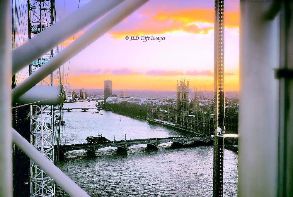 """... London was sprawling, dirty and happily voluptuous, in the yellow evening sun ..."" Margery Allingham, The Fashion in Shrouds. Riverscape of the Thames from the top of the London Eye at sunset, showing Westminster Bridge and Houses of Parliament.  Machinery and tubular supports of the London Eye frame the view."