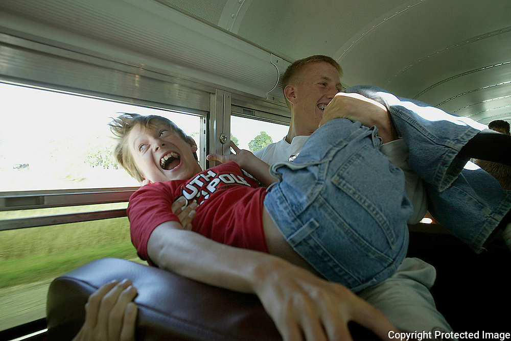 """Freshman David Vande Zandschulp gets his initiation to his first MOC-Floyd Valley band field trip as junior Matt Roesner playfully holds his head out the window of their bus which was enroute to Marshall, Mn.  At the competition that night, Vande Zandschulp admitted to being scared.  """"Once the music started, I felt in the groove,"""" said the trumpet player."""