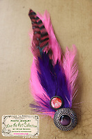 """Rose photo fascinator with vibrant feathers handmade with love by Star Nigro<br /> <br /> This handcrafted wearable art piece can also be clipped to a blouse,pocket book,hat etc. <br /> <br /> Materials: rose photo,pink & purple colored feathers,with purple glass accent, barrette clip<br /> <br /> size: 2"""" x 7"""" x1/4""""<br /> <br /> price: $52.00<br /> <br /> <br /> + Giveback<br /> When you make a purchase from this site will be shared with a non-profit that focuses on making a positive difference in the world today.<br /> <br /> Buying art  + Making a difference = Art with Heart"""