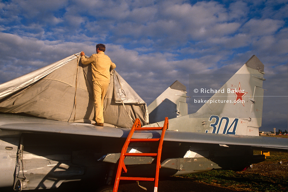 "A Migoyan technician covers a Mikoyan MiG-29 fighter jet as it makes its first ever display appearance to a western air show audience. The Mikoyan MiG-29 or ""Fulcrum"" is a fourth-generation jet fighter aircraft designed in the Soviet Union for an air superiority role. Developed in the 1970s by the Mikoyan design bureau, it entered service with the Soviet Air Force in 1983, and remains in use by the Russian Air Force as well as in many other nations."