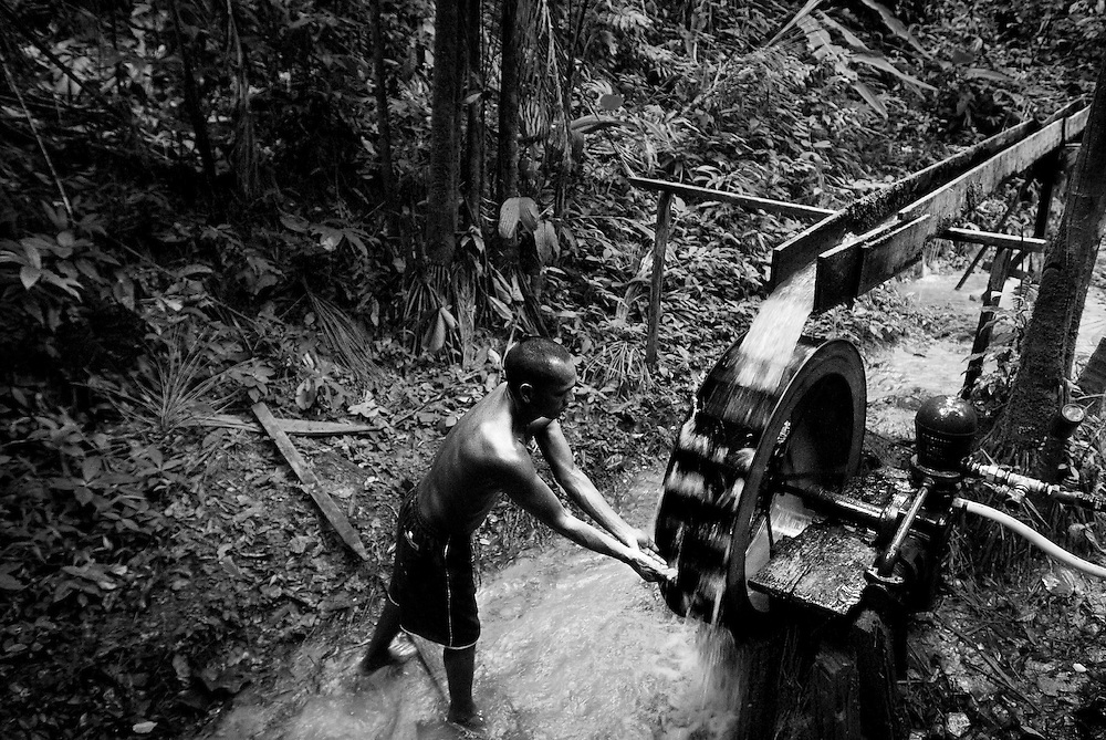 """BRAZIL, SANTAREM REGION, AMAZON. NOVEMBER 2008. A man next to a """"water wheel"""", system used to provide water to the houses in the Amazon jungle."""