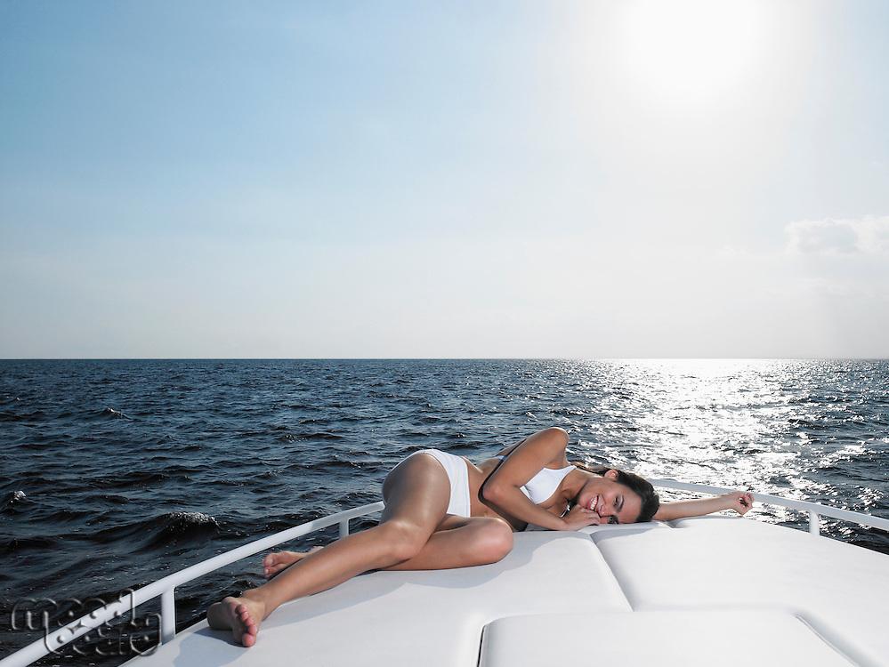 Young woman in bikini relaxing on yacht