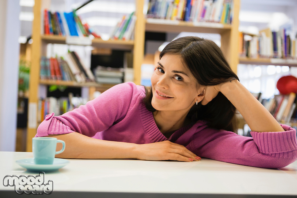 Portrait of young woman with coffee on desk in library
