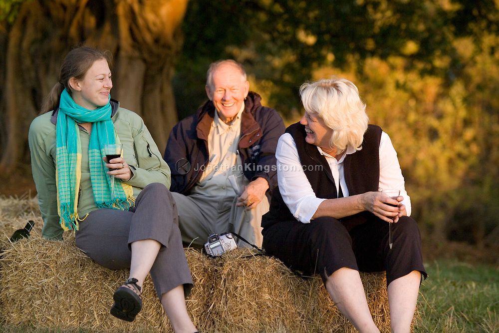 Sarah, Jody and Fred Stark enjoy a glass of wine in a field at sunset near the Glenshiel Hotel in South Africa's Drakensberg Mountains. (Model Released)