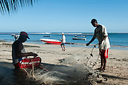 Fisherman Herve Mariane (seated) repairs his nets. Morning. Tamarin.