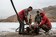 Workers check their machinery after completing field repairs on the frozen crust of the Mekong river. The team is taking earth samples from the river bed in preparation for the construction of a new bridge over the Mekong in Zado, Tibet (Qinghai, China).