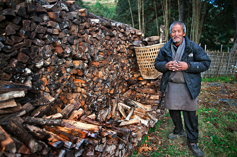 A man in Bumthang, Bhutan collects firewood from his winter stockpile.