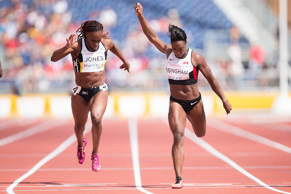 Khamica Bingham (R) of Canada edges Laverne Jones  of the US Virgin Islands in the hears of the women's 100 metres on the first day of athletics at the 2015 Pan American Games in Toronto, Canada, July 21,  2015.   AFP PHOTO/GEOFF ROBINS
