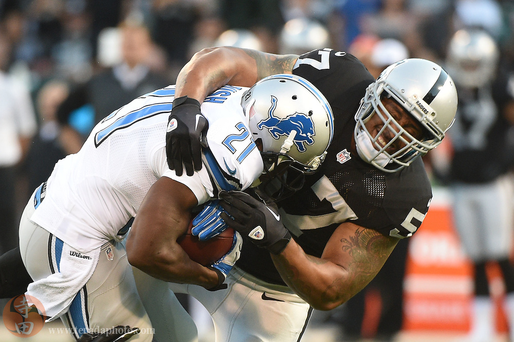 August 15, 2014; Oakland, CA, USA; Detroit Lions running back Reggie Bush (21) is tackled by Oakland Raiders defensive end LaMarr Woodley (57) during the first quarter at O.co Coliseum.