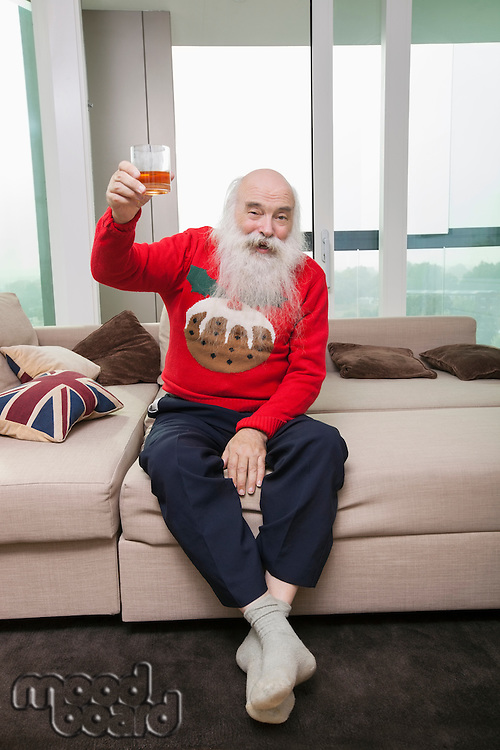 Full length portrait of senior man holding beer glass in living room