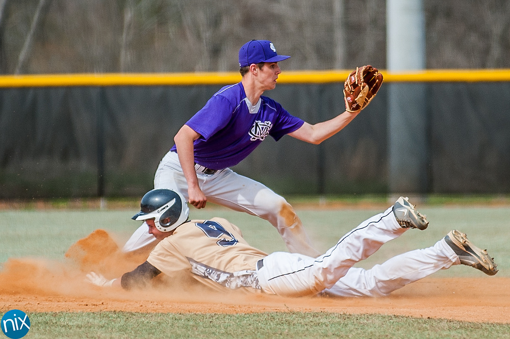 First Assembly's Ryan Kirk slides into second base as Cox Mill's Hunter Longmire waits on the throw Wednesday afternoon at Cox Mill High School. Cox Mill won the game 2-1.