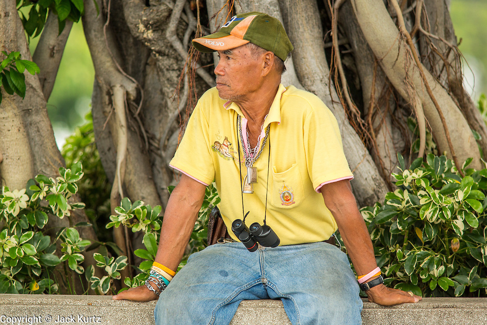 27 SEPTEMBER 2012 - BANGKOK, THAILAND:  A Thai man wearing a yellow shirt waits for the rehearsal of the Royal Barge Procession to reach Tha Tien Pier in Bangkok. Thais frequently wear yellow at events tied to the Royal family because yellow is considered the King's color. The Thai Royal Barge Procession is a ceremony of both religious and royal significance that goes back almost 700 years. The Royal Barge Procession takes place rarely, typically coinciding with only the most significant cultural and religious events. This year there will be a full procession on November 9 to mark the end of Buddhist Lent. During the reign of King Bhumibol Adulyadej, spanning over 60 years, the Procession has only occurred 16 times. The barges are manned by 2,082 oarsmen. The Procession proceeds down the Chao Phraya River, from the Wasukri Royal Landing Place in Khet Dusit, Bangkok, passes the Temple of the Emerald Buddha, the Grand Palace, Wat Po and arrives at Wat Arun (the Temple of the Dawn).   PHOTO BY JACK KURTZ