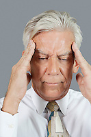 Close-up of senior businessman with headache over gray background