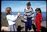 Eva Valsdottir, 9, shows feisty puffin chick to friends before releasing it to sea on Heimaey. Iceland
