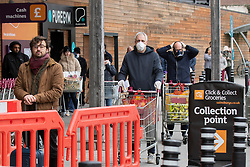 © Licensed to London News Pictures. 31/03/2020. London, UK. Shoppers in face masks queue to enter Sainsbury's supermarket in Charlton South east London. The Government has announced a lockdown to slow the spread of Coronavirus and reduce pressure on the NHS. Photo credit: George Cracknell Wright/LNP